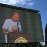 """Dr. Sarkar on the """"big screen,"""" addressing the crowd at the US IYD event, June 21, 2015."""